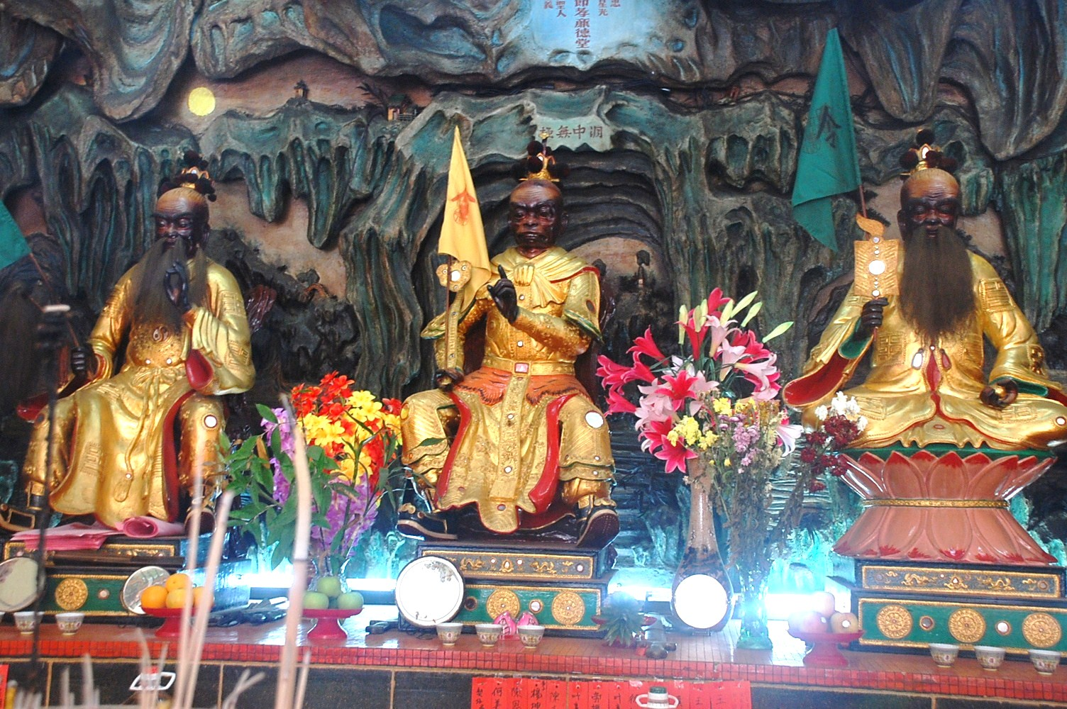The three deities at the main altar: Wong Loo Sen See (left) represents Confucianism, the Chai Tin Dai Sing or Monkey God (centre) represents Buddhism and the Tai Siong Lou Guan (right) represents Taoism.