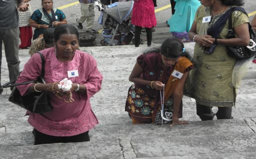 Susilasusaymary, 55, years old (left) on her knees going up the steps (20 steps) to the Shrine