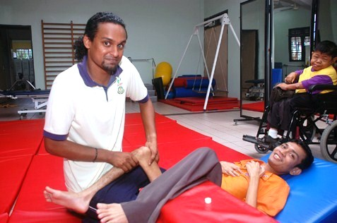 Physiotherapist Kiram Sam Raji (left) giving treatment to a patient