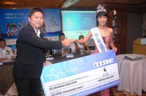 Brian of Scubawalker.com presents a mock cheque to Dayu P Hatmanti