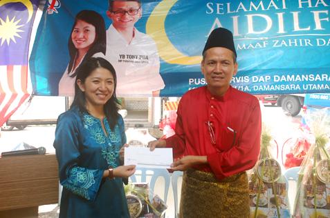 Persatuan Penduduk Rumah Pangsa Damansara Bistari chairman Abdul Samad Abdul Rashid receives a contribution from Yeo Bee Yin.