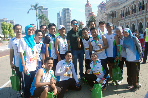 Youth and Sports minister Khairy Jamaluddin (centre, with sunglasses) posing with participants after the marathon race.