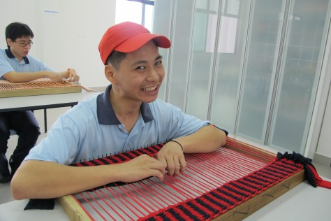 19-year old Chen Yee How weaving a floor rug for sale in the thrift shop