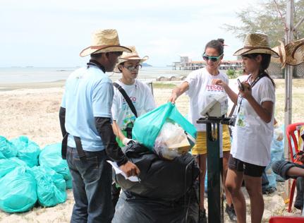 Tesco employees collecting litter along Port Dickson beach