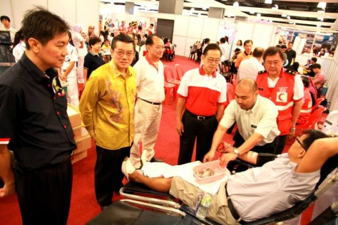 Mr Mok chatting with a donor and flanked by Rotary club members