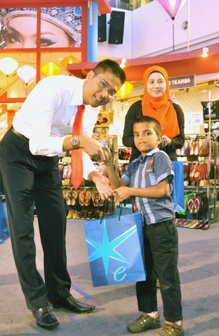 Azizul Hisham Ahmad, Centre Manager of eCurve distributing CNY goodies to the children of Agathians Shelter