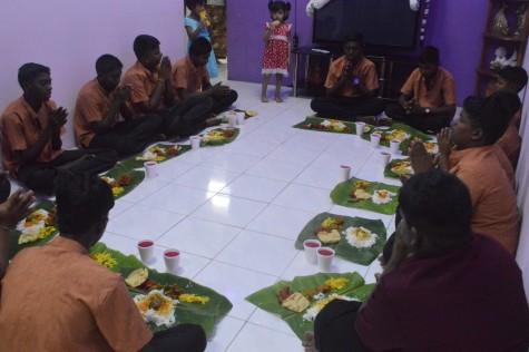 Children from the ashram saying their prayers before enjoying their dinner
