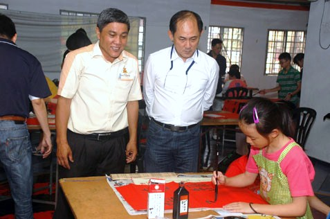 MBPJ councillor Sean Oon Chong Ling (right) and JKKK Sg Way chairman Ding Eow Chai looking at Koh's calligraphy skill.