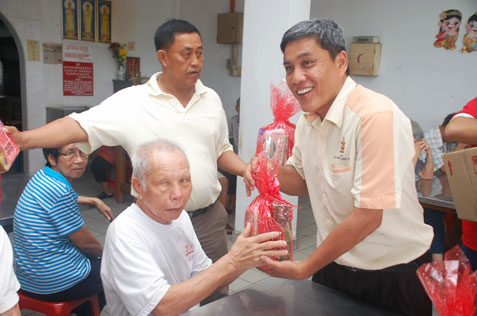 JKKK Sungai Way chairman Ding Eow Chai presenting mini hamper to a senior citizen at Rumah Sejahtera Seri Setia Sungai Way