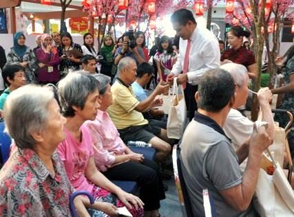 Jazmi Kamarudin distributing ang pow and goodie bags to senior citizens