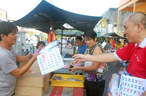 Lau Weng San distributing 2014 calendars to hawkers in SEA Park