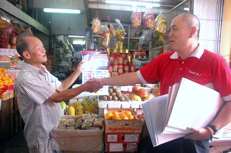 Lau Weng San handing out 2014 calendars to market traders in SEA Park