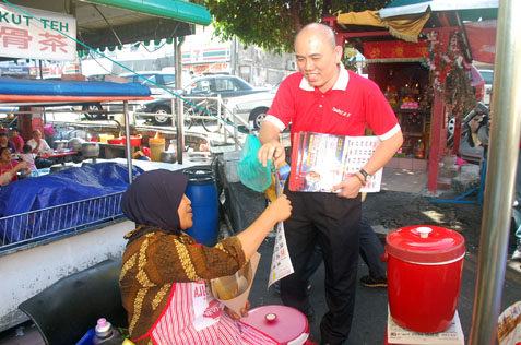Lau Weng San handing out calendar to nasi lemak seller in SEA Park