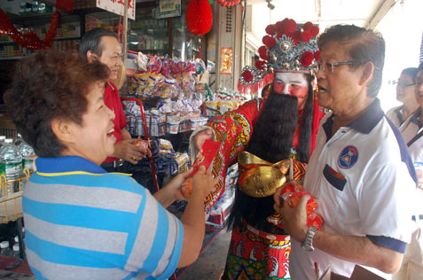 A woman happy to receive ang pow from Choy San Yeh