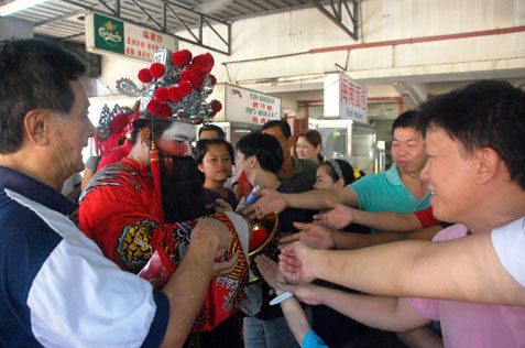 God of Prosperity giving out ang pow to patrons at Khoong Coffee Shop Sea Park