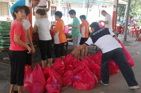 Volunteers help to fill the bags with groceries for the senior citizens