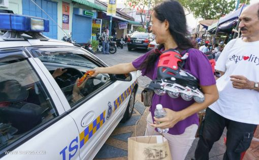 Two policemen inside a police car also received carnations! (Picture by Ch'ng Shi P'ng)