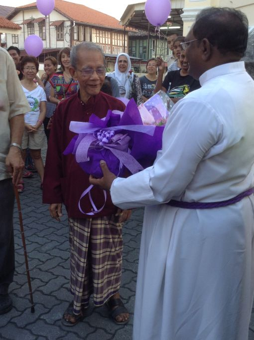 Venerable Charles Samuel presented a bouquet of flowers to Mohamed Yahaya.