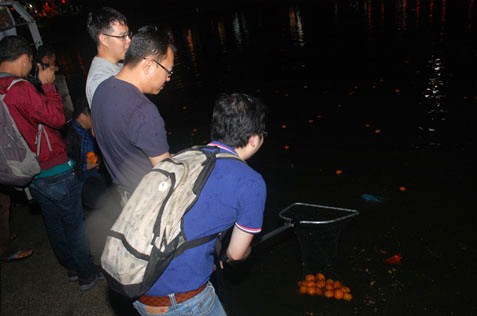 A big catch of oranges for this man at Taman Jaya lake on Chap Goh Meh
