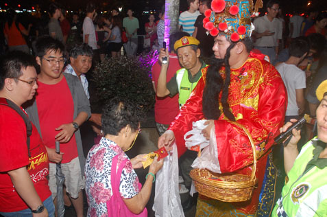 God of Prosperity distributing ang pow on Chap Goh Meh night at Taman Jaya lake
