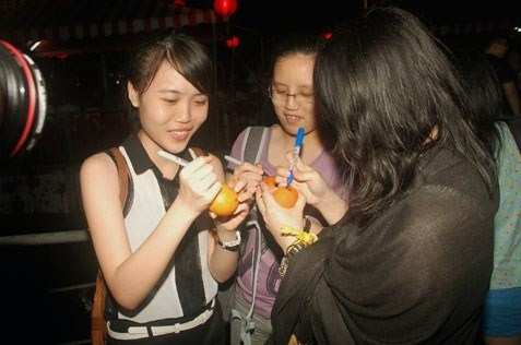 Young ladies writing their names and contact numbers on oranges before throwing into the lake in hopes of finding love.