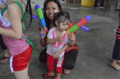 Mom and daughter with water gun enjoying enjoying the festival
