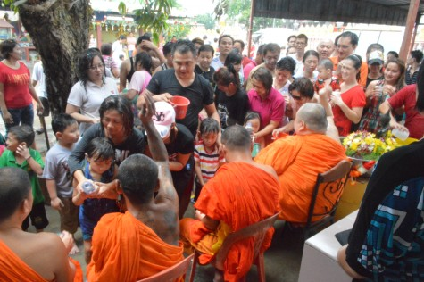 Devotees also taking turns to sprinkle onto the Monks
