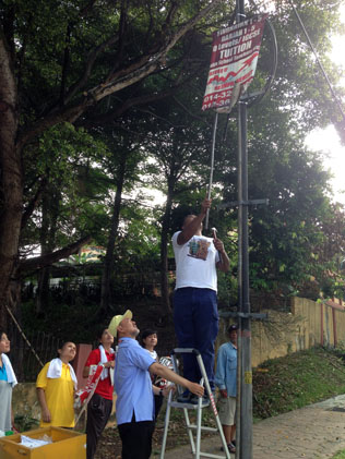 MBPJ councillor Oon Chong Ling and volunteers removing illegal banner attached to lamp post