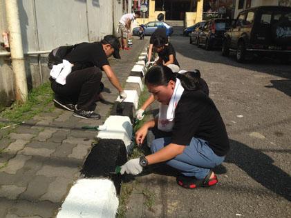 Volunteers painting road side kerbs