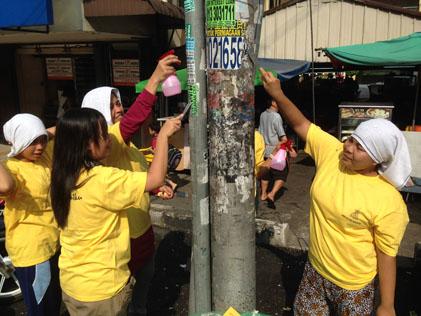 Volunteers scraping stickers off lamp post