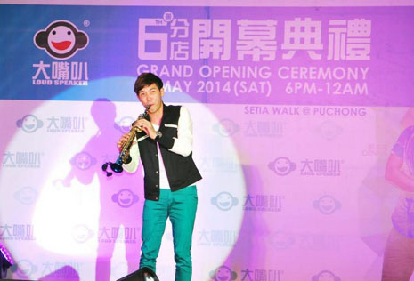 Keith Tan playing the saxophone to the crowd's delight.