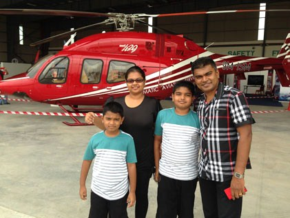 Selva Ganesan and family at the 1st Subang International Air Carnival 2014, posing in front of a Bell 429 helicopter