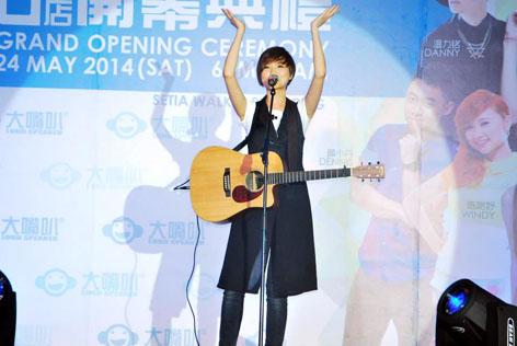 Singapore singer and songwriter Ling Kai singing while strumming the guitar