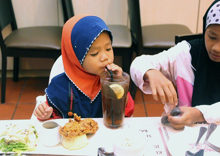 Children from Rumah Amal Suci Rohani breaking fast at eCurve's Buka Puasa event.