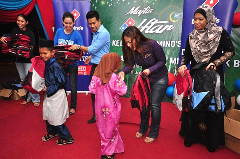 Shamsul Amree (in blue shirt) and Hasfahlinda Hassan presenting children of Pertubuhan Kebajikan Anak-Anak Yatim & Miskin Sabak Bernam with school supplies