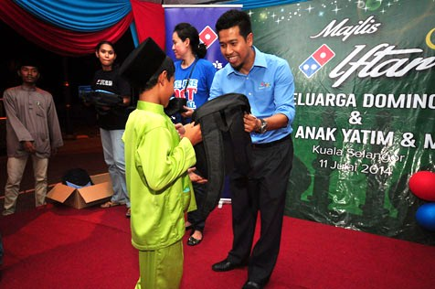 Shamsul Amree presenting school bags filled with school supplies to orphans from Pertubuhan Kebajikan Anak-Anak Yatim & Miskin Sabak Bernam
