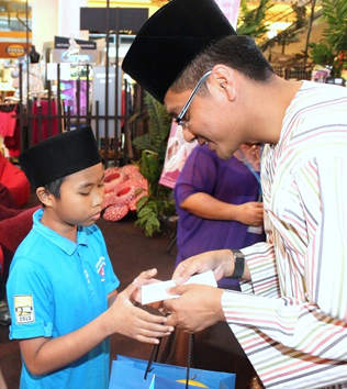 eCurve centre manager Azizul Hisham handing out duit raya to orphans