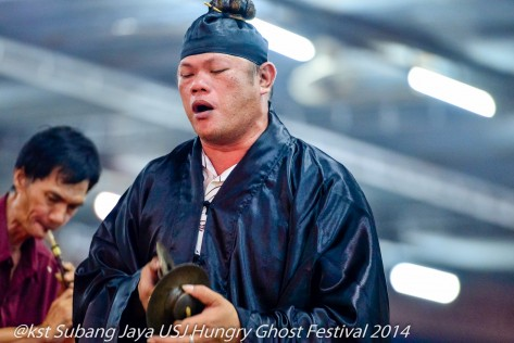 A Toaist priest chants to appease  the Hungry Ghosts