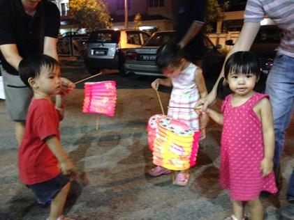 Childen enjoying themselves holding their lighted lanterns