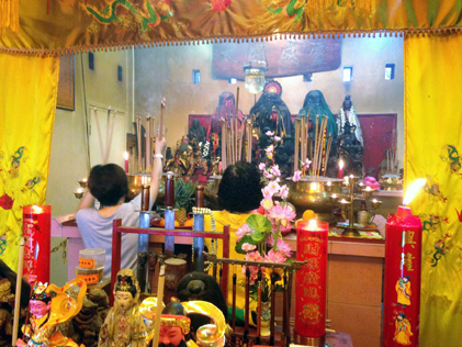 Devotees solemnly pray before the altar of Huat Chu Kong