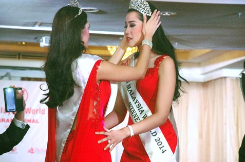 Dewi Liana Seriestha being crowned Miss Malaysia World 2014 by her predecessor Melinder Bhullar, the Miss Malaysia World 2013