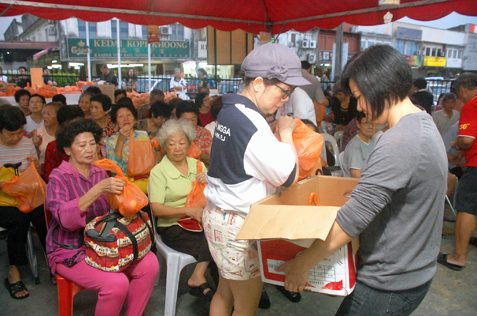 Committee members distributing goody bags to senior citizens.