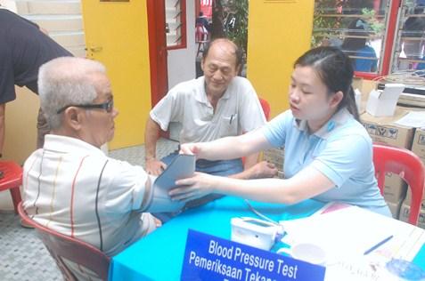 Pfizer Care-A-Van volunteer conducting health check