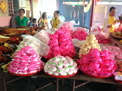 Special offerings of mee koo (red tortoise buns), ang koo (red tortoise cakes), fruits and whole roast pigs for the deities.