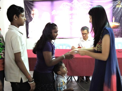 Yeo handing out little packets to children at the Deepavali lunch treat