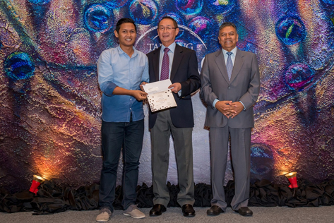 Muhammad bin Abdullah, first prize winner of the Print Making category receiving his certificate and prize from Tanjong PLC chairman Dato' Robert Cheim. Looking on is GCFO Gerard Nathan