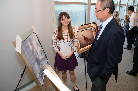 Tanjong PLC chairman Dato' Robert Cheim viewing the first prize artwork in OilAcrylic categorty by Tham Yoke In of Dasein Academy of Art.