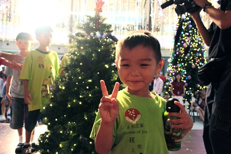 A young guest grins at the camera as the children take turns decorating a mini Christmas tree at the Curve