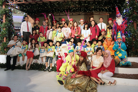 Big smiles all around in a group photo with Jazmi Kamarudin (standing, far left), management team, performers and guests from House of Joy