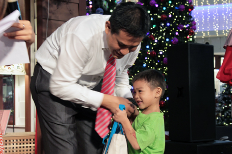 The Curve centre manager Jazmi Kamarudin hands out Christmas goodies to the children of House of Joy